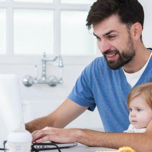 padre-che-lavora-al-computer-portatile-mentre-si-tiene-bambino-1600x800